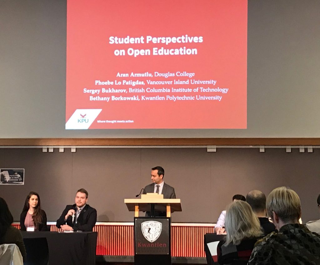 "Four students seated with one moderator standing between them. One of the students is speaking. The screen above the group reads ""Student Perspectives on Open Education"""