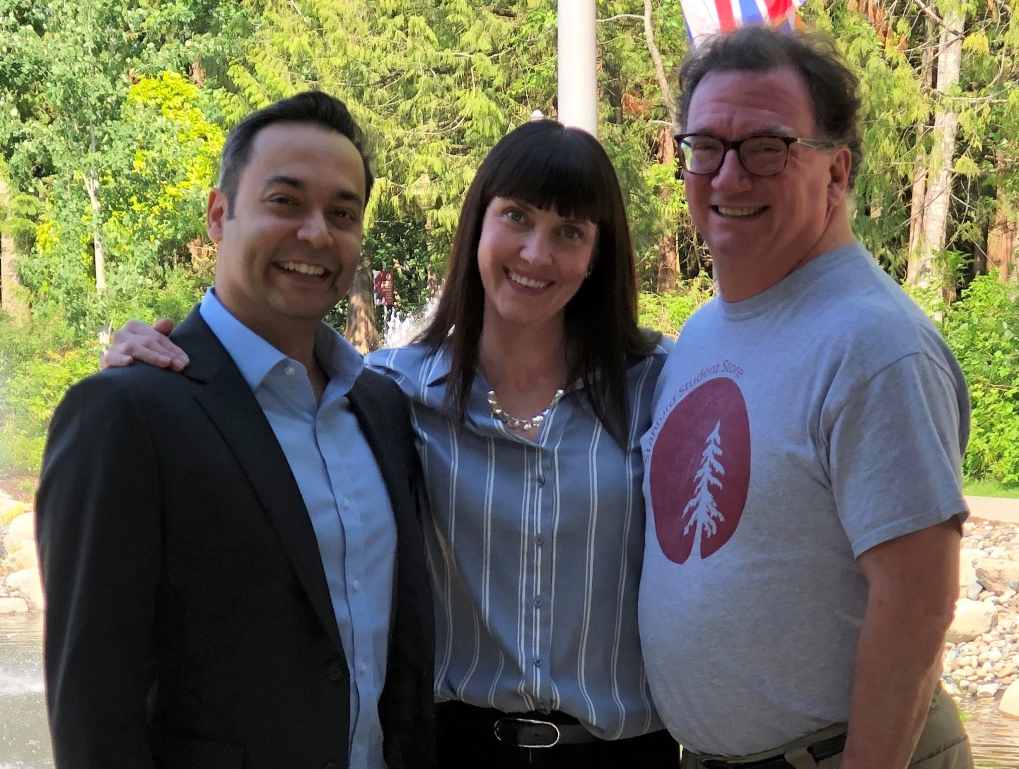 Rajiv Jhangiani, Carrie Cuttler, and Dana Leighton smiling while standing in front of greenery and a partly-obstructed flag pole.