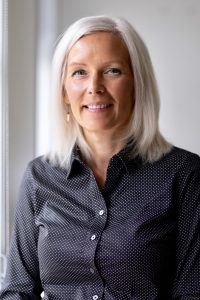 Brenda Knights headshot. Middle aged woman with white hair and symmetrical oval shaped face wearing a black buttoned up shirt