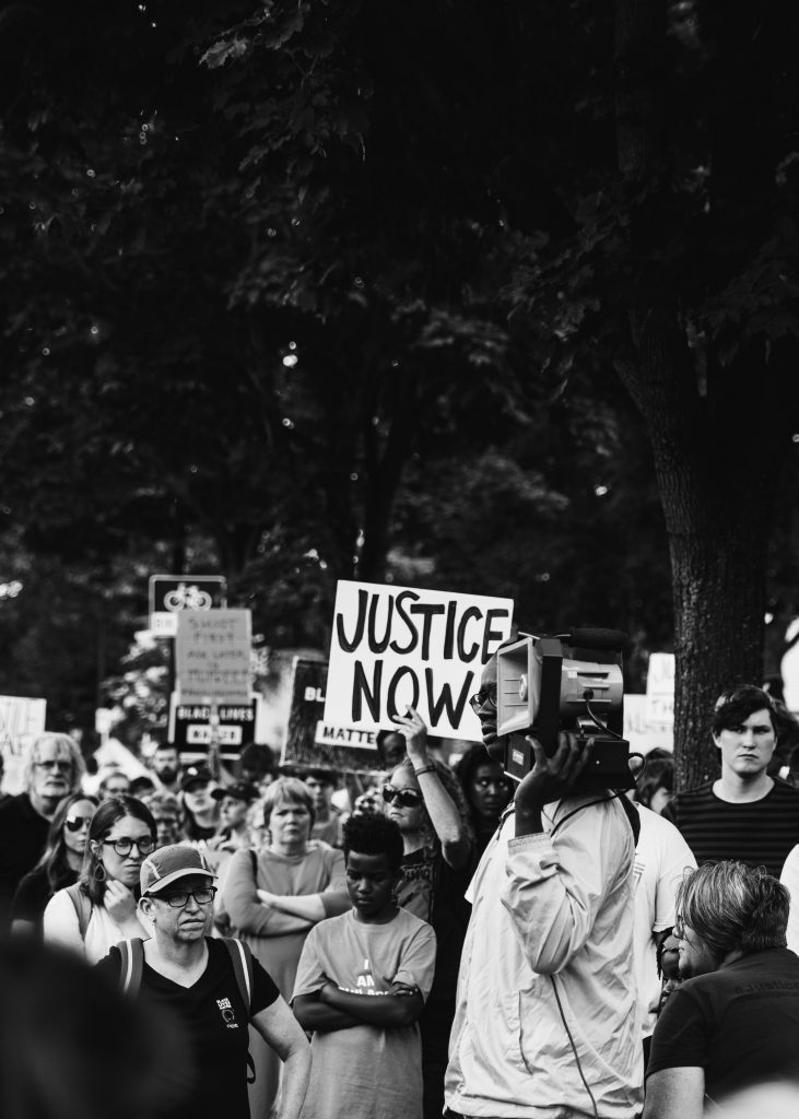 A black and white image of a protest. Someone holds a sign saying 'justice now'