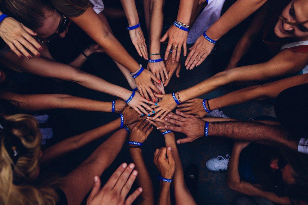 Teammates put their hands in a circle.