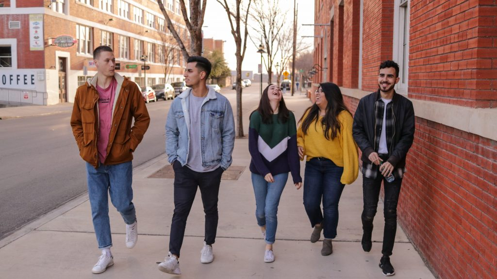 Five college/university-aged students walking down a sidewalk together talking and laughing.