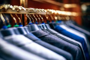 Mens' luxury blazer and suit tops on hangers in a closet.