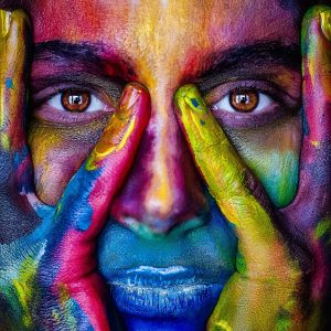 A model's face with hands on sides adorned with several bright colours painted on their skin.