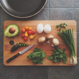 A knife and chopping board with various vegetables and two eggs.