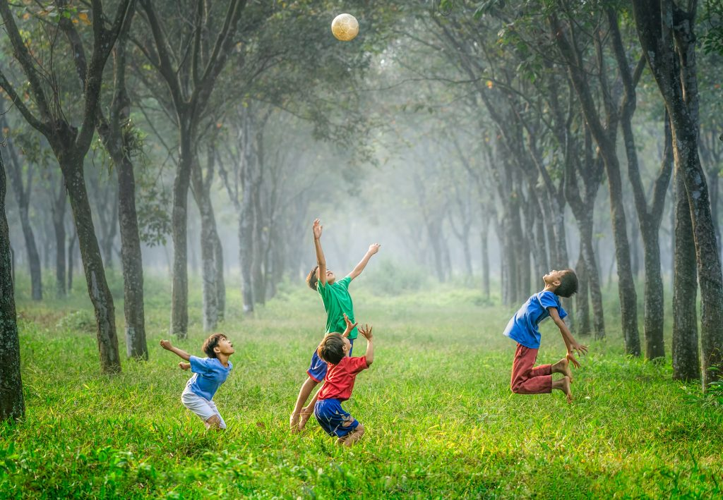 Four children playing with a ball in a field surrounded by trees.