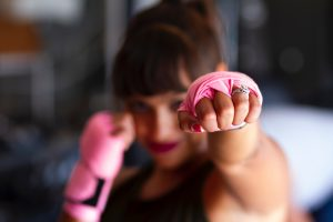 Woman with pink hand wraps air boxing; wraps are pink to represent the Pink Ribbons movement.