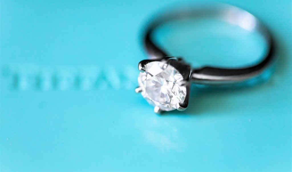 Photo of a diamond engagement ring against a robin's egg blue box that is presumably the brand, Tiffany's