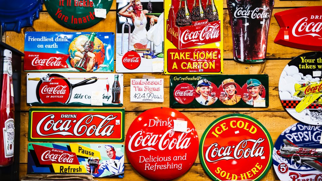 Collage featuring vintage Coca-Cola logos on various products and memorabilia.