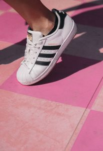 Person's foot, wearing Addidas Superstar shoes; white with black stripes.