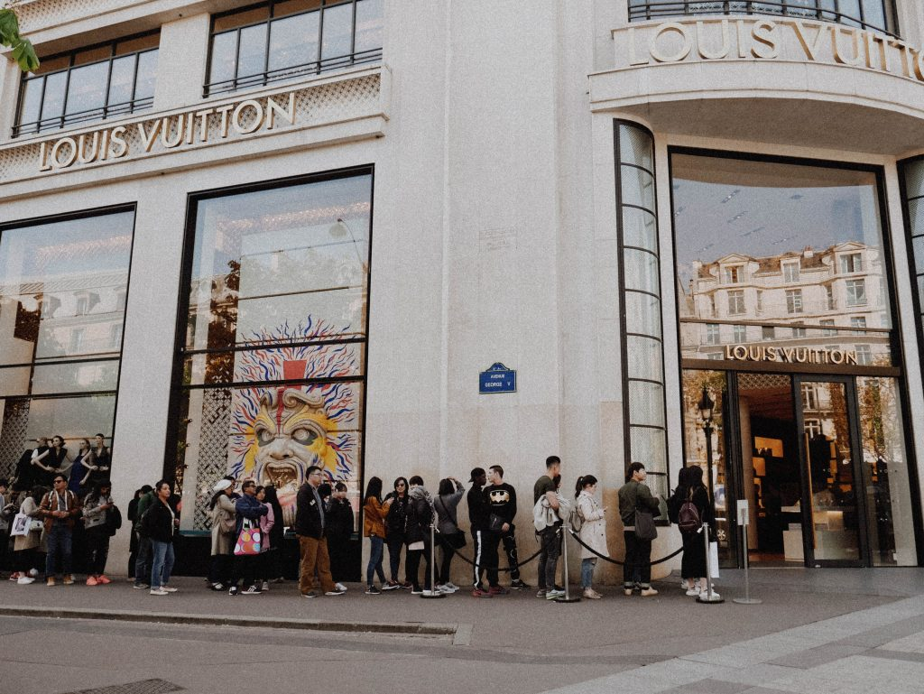 Long line of customers outside a fashion retailer waiting to enter the store.