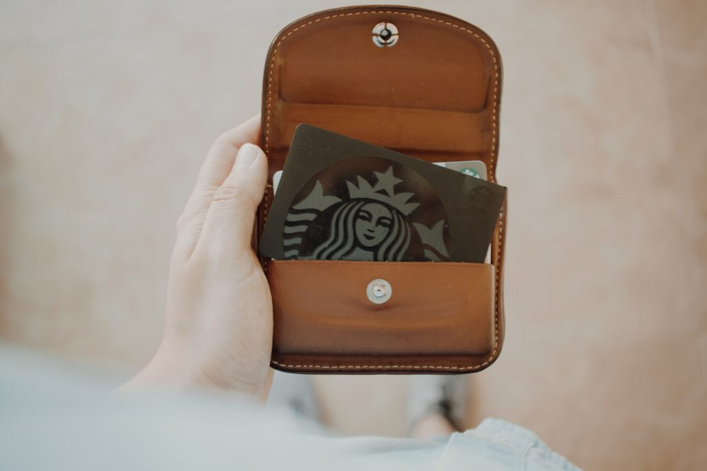 Person's hand, holding a wallet that contains a Starbucks card.