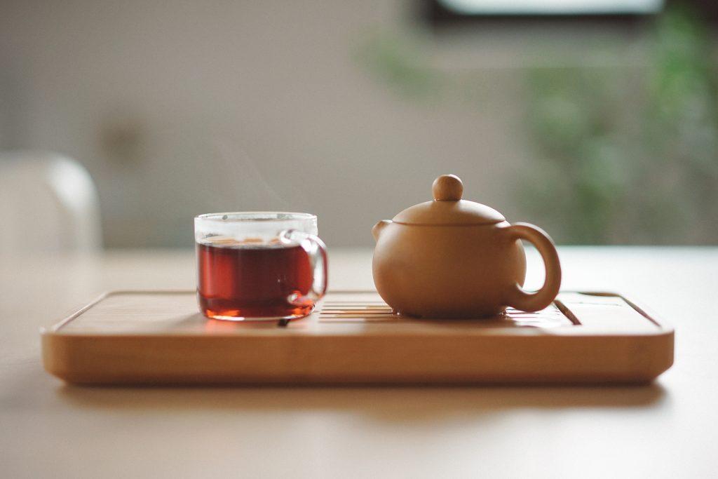 Clear mug with tea next to a tea pot.