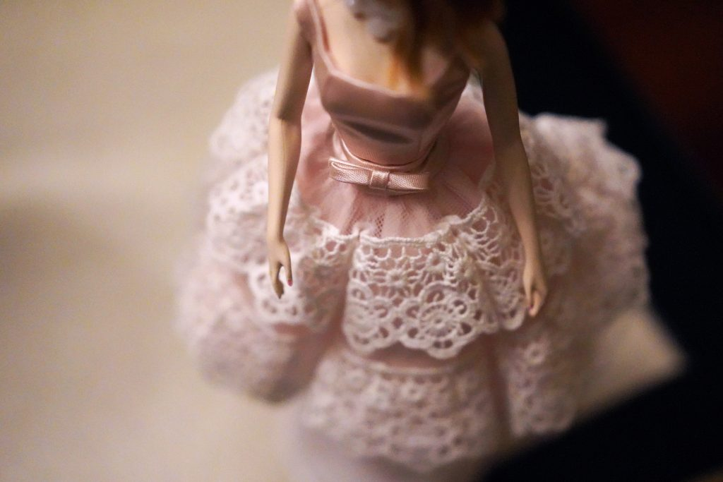 Barbie doll figure wearing pink dress with white lace in the skirt portion.